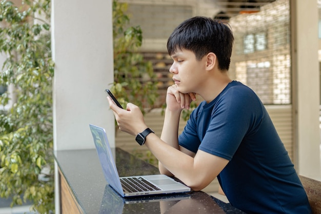 Online studying concept the young man in deep blue t-shirt and black watch using his smartphone to call his friends because they don't show up on online meeting at the moment.