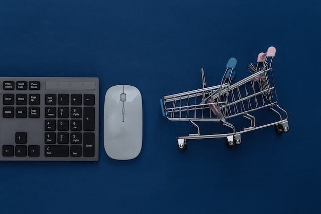 Online supermarket. pc keyboard and shopping trolley on a classic blue