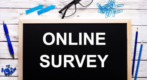 Online survey written on a black noteboard next to blue paper clips, pencils and a pen.
