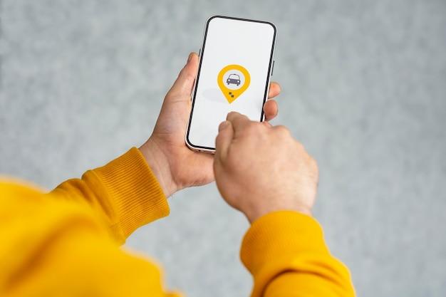 귀하의 휴대 전화에 온라인 택시. 한 남자가 흰색 화면과 택시의 지리적 위치 및 위치 아이콘이 있는 스마트폰을 들고 있습니다.