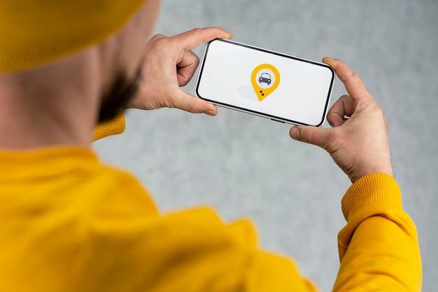 휴대 전화에서 온라인 택시. 한 남자가 흰색 화면과 택시의 위치 정보 및 위치 아이콘이있는 스마트 폰을 들고 있습니다.