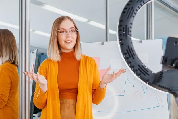 온라인 교사는 비디오 수업을 녹화합니다. 관리자는 온라인 회의 중에 프레젠테이션을 합니다. 여자는 화이트 보드에 그래픽을 할. 원격 작업. 코치 멘토 또는 학생은 교육 과정을 라이브 교육으로 만듭니다.