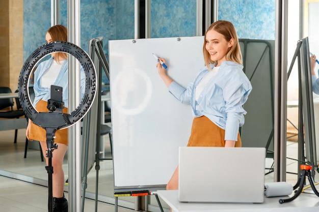 Женщина-учитель онлайн пишет на доске в пустом классе, записывая живую тренировку, использует смартфон лампы blogger, ноутбук. вебинар по электронному обучению. социальная дистанция из-за изоляции covid в новом нормальном образовании.