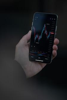 Интернет-трейдинг. обрезанный снимок трейдера или инвестора, который читает финансовые новости в режиме реального времени и проверяет данные фондового рынка в современном мобильном приложении на смартфоне. выборочный фокус на экране с графиком форекс