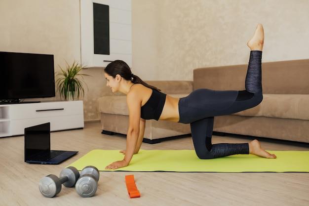 집에서 온라인 교육. 집에서 운동하는 젊은 여자.