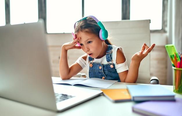 Онлайн-обучение. ребенок девочка в наушниках слушает урок на ноутбуке. школа дома в условиях пандемии и карантина.