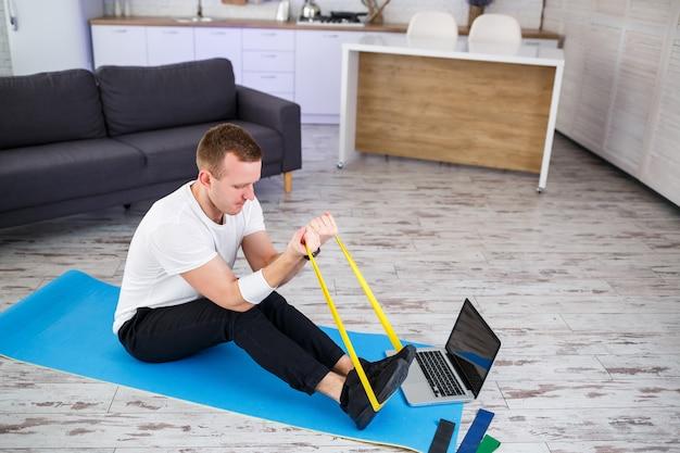 Онлайн-обучение. человек делает упражнения с резинками дома, свободное место. заниматься спортом дома