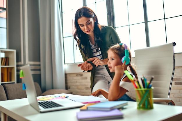 オンライントレーニング。ママは娘のレッスンを手伝います。ヘッドフォンの女子高生は、ラップトップでレッスンを聞いています。パンデミックと検疫で自宅で学校。