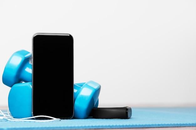 Онлайн-обучение. спортивные устройства. обучение музыке. гантели, смартфон, наушники и фитнес-браслет. скопируйте пространство на дисплее смартфона. здоровый образ жизни. период изоляции. домашние упражнения.