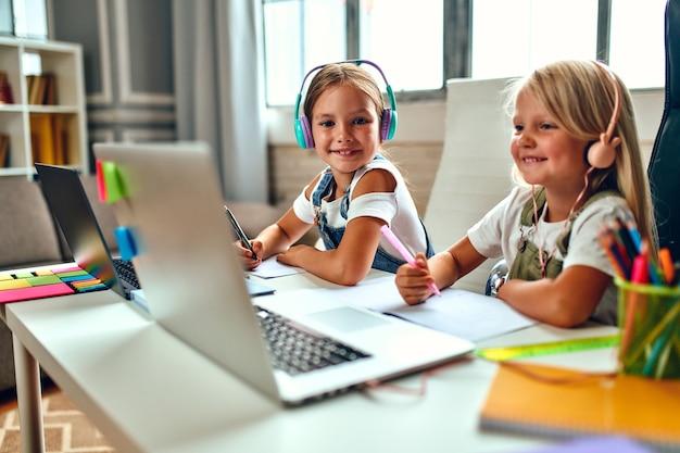 Онлайн-обучение. две сестры-школьницы в наушниках слушают уроки на ноутбуках. школа дома в условиях пандемии и карантина.