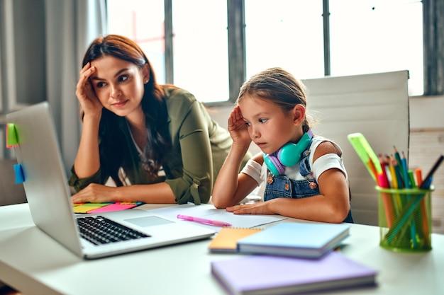 オンライントレーニング。非常に難しいレッスン。彼女の母親と一緒の女子高生はラップトップでレッスンを聞きます。パンデミックと検疫で自宅で学校。