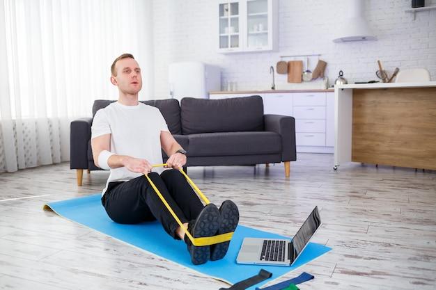 Онлайн-обучение. молодой человек делает упражнения с фитнес-резинками с онлайн-учебником дома, свободное место. заниматься спортом дома