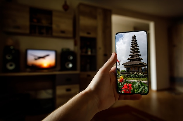 Online travel to bali island via mobile phone from home.