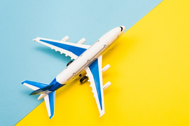 Online travel booking concept. airplane model and passport on yellow and blue background. abstract runway