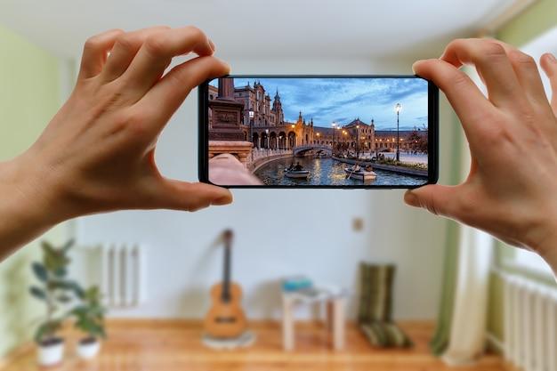 집에서 휴대 전화를 사용하여 스페인 세비야로 온라인 여행. 스마트 폰 화면의 plaza de espana