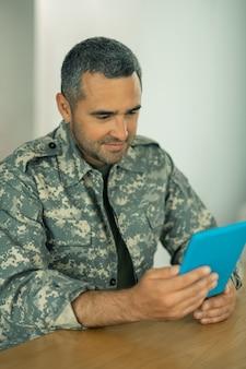 オンラインビデオチャット。妻とオンラインビデオチャットをしているハンサムなひげを生やした軍の将校