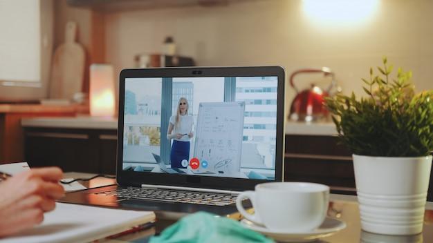 Онлайн видеоконференция на ноутбуке с говорящей женщиной в домашнем офисе