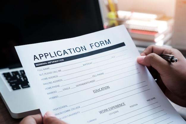 オンラインweb求人応募フォームのコンセプト。申請書の形でメモをとってテーブルに座っている認識できないビジネスマンのクローズアップ