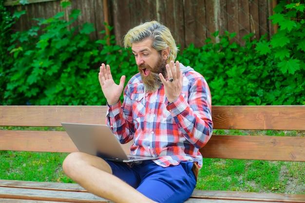 Онлайн-победитель взволнованный мужчина с ноутбуком в парке цифровой работой взволнованный мужчина с ноутбуком на открытом воздухе онлайн