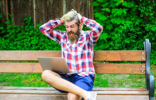 Online winning excited man with laptop at park digital work online game freelance money game online