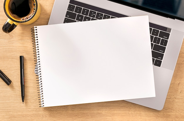 Online work or education concept blank notebook with laptop and cup coffee on wooden table top view