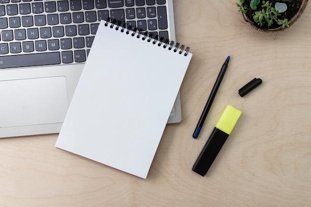 オンラインでの仕事、教育、またはフリーランス。空白のメモ帳はラップトップでクローズアップします。