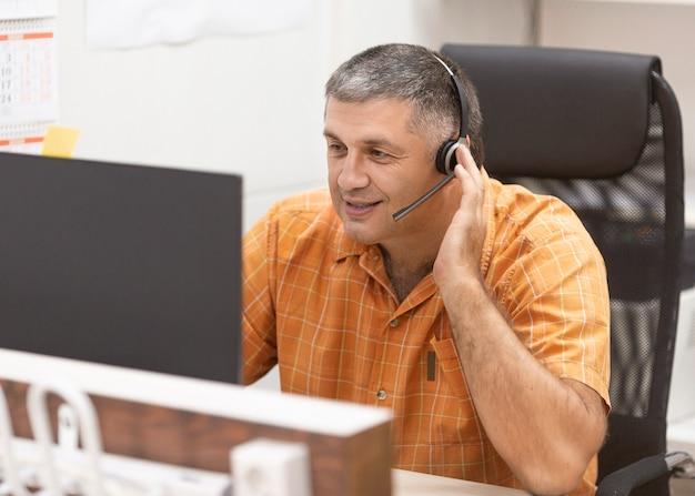 オンライン作業のコンセプト。オンラインで会話するヘッドセットを持つスマイリー男。ビジネスの肖像画。