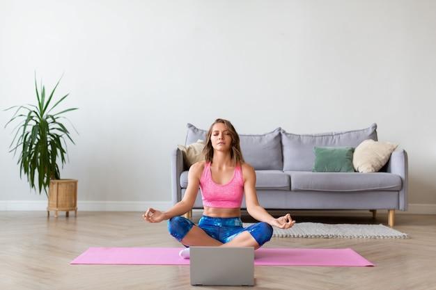 Онлайн-урок йоги. женщина в позе лотоса перед монитором ноутбука.
