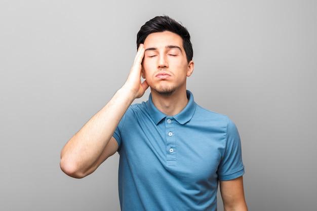 Только плохие новости. измученный взрослый человек в синей рубашке с головной болью, держа руку на виске, стоя на сером фоне