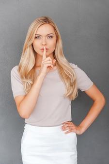 あなたと私の間だけ!美しい若い女性と唇に指を保持します。