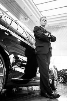 Только элитные автомобили. черно-белое изображение уверенного в себе человека с седыми волосами в полный рост в формальной одежде, облокачивающегося на машину и смотрящего в сторону