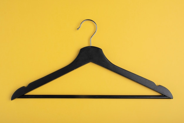 Only one black wooden hanger isolated on yellow background.