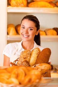 Только лучшая и свежая выпечка. красивая молодая женщина в фартуке, держащая корзину с выпечкой, стоя в пекарне