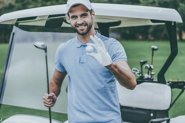Только лучшее снаряжение для гольфа! красивый молодой улыбающийся человек, держащий мяч для гольфа и водителя, стоя рядом с тележкой для гольфа и на поле для гольфа