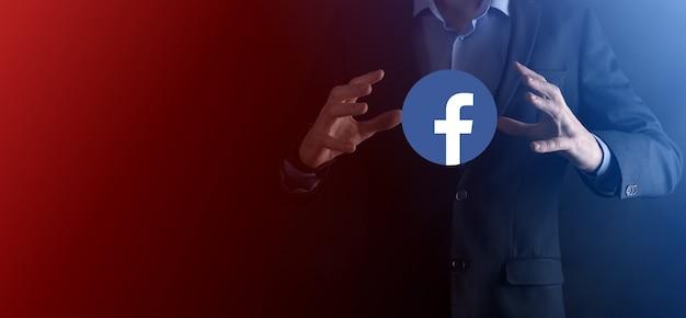 ウクライナ、オノク-2021年7月14日:ビジネスマンがfacebookアイコンを手に持ってクリックします。ソーシャルネットワーク。グローバルネットワークとデータ顧客接続。国際ネットワーク。