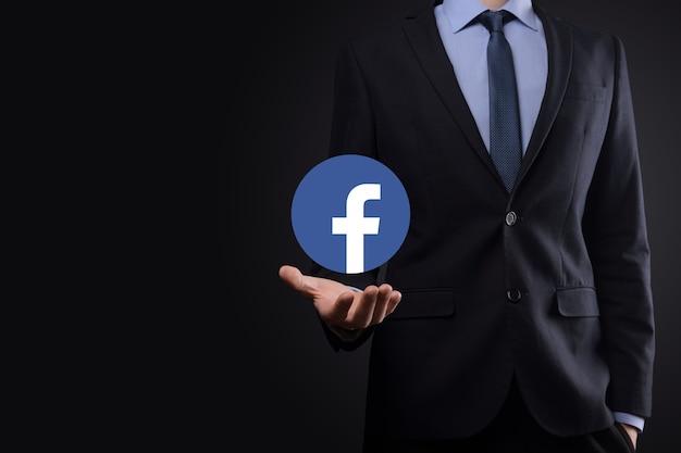 우크라이나 오녹 - 2021년 7월 14일: 사업가가 손에 facebook 아이콘을 잡고 클릭합니다.소셜 네트워크.글로벌 네트워크 및 데이터 고객 연결.국제 네트워크.