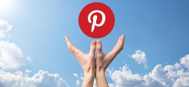 우크라이나 오녹 - 2021년 7월 14일:사업가가 손에 들고 클릭하고 핀터레스트 아이콘을 들고 있습니다.소셜 네트워크.글로벌 네트워크 및 데이터 고객 연결.국제 네트워크.