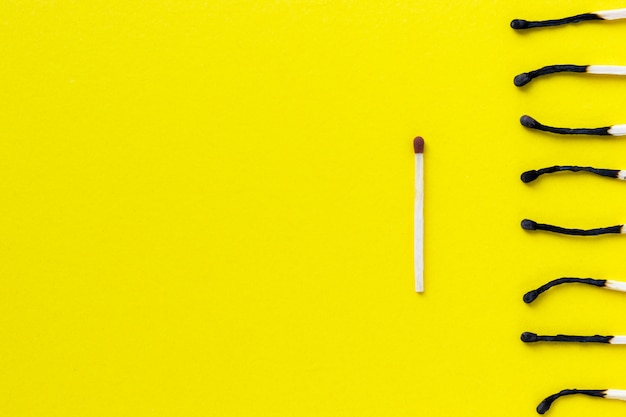 Onr unused and group of burnt out match sticks on yellow background