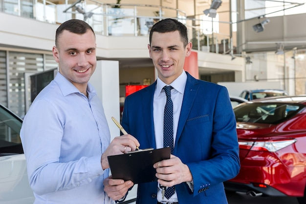 Ðâ¡onsultant signs the documents with buyer on car