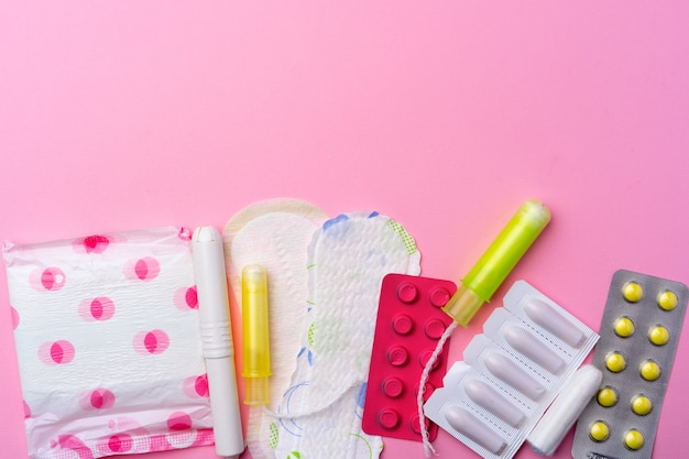 Ðâ¡ontraceptive pills, hygienic pads and tampons on pink top view