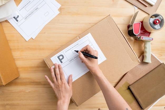 Вид рук молодой женщины-менеджера интернет-магазина, держащей черный маркер на бланке для адреса клиента на упакованной коробке