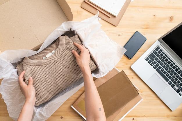 Вид на руки молодой женщины-менеджера интернет-магазина, складывающей сложенный бежевый вязаный свитер в коробку перед его упаковкой и отправкой клиенту