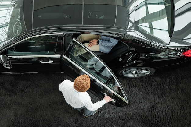現代の自動車センターの若いマネージャーが試乗する前にクライアントを中に入れて豪華な黒い車のドアを閉める様子