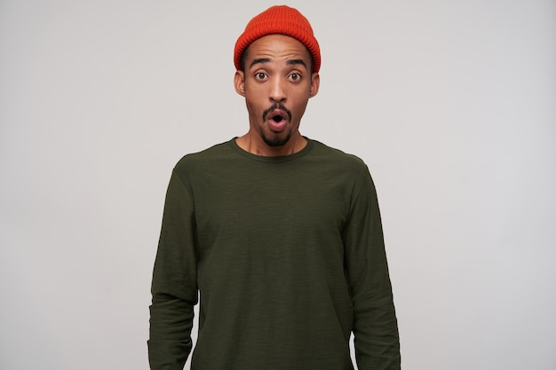 Onwhelmed young bearded brunette male with dark skin looking amazedly with round eyes, wearing red hat and khaki sweater on white