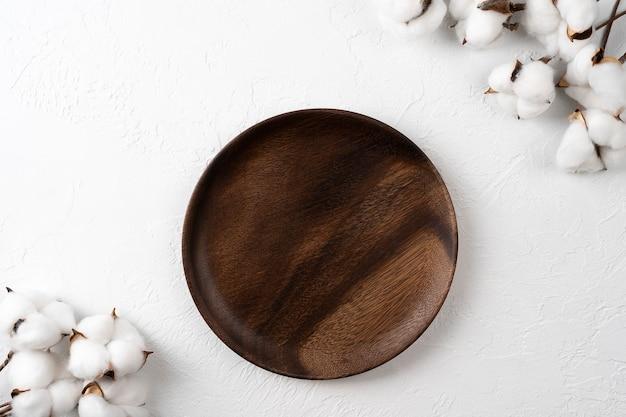 Ooden тарелка с цветами хлопка на белом фоне элегантная минималистская сервировка стола вид сверху