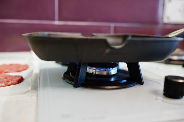 検疫時間中に自宅のキッチンでハンバーガーを調理する。ガスストーブのフライパン