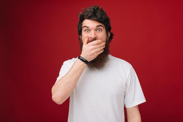 Oops! close up portrait of bearded man closed his mouth with hand and wide opened eyes, , he can't believe his eyes, standing over red wall