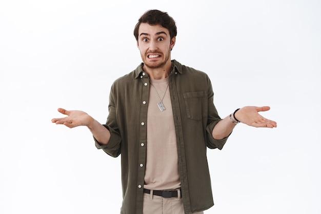 Oops colpa mia, scusa non lo sapevo. un ragazzo imbarazzante e carino hipster che dice yikes alzando le spalle e lanciando le mani indeciso, non posso dirlo