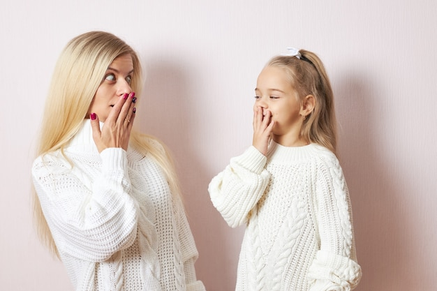 Oops, omg. adorable little girl and her young mother both in white sweaters posing isolated keeping hands on mouths, being astonished with big sale prices, going shopping to buy christmas presents