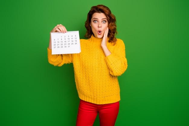 Ой! фотография довольно шокированной женщины держит бумажный календарь с изображением руки планировщика на щеку, боясь забеременеть, в желтом вязаном свитере красные штаны изолированы на стене зеленого цвета